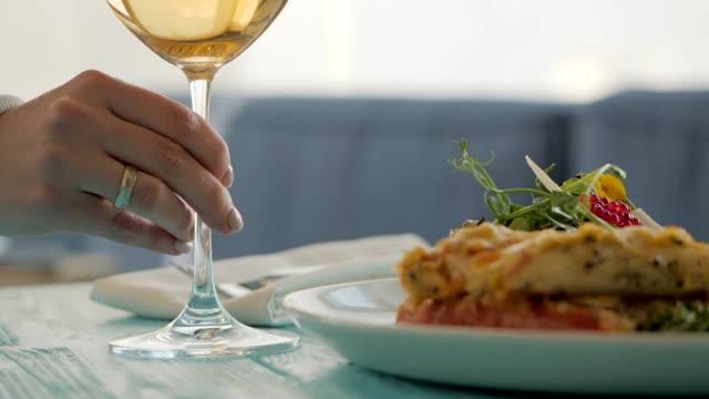 tisch im restaurant. schüssel mit salat von meeresfrüchten, kaviar, gemüse und grünen. weibliche hand nimmt ein glas weißwein zur verkostung. glücklich festlichen moment, luxus-feier-konzept - champagner toasts stock-videos und b-roll-filmmaterial