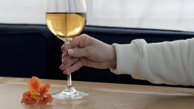 tisch im restaurant mit frischen blumen. weibliche hand nimmt ein glas weißwein zur verkostung und legt ihn zurück. glücklich festlichen moment, luxus-feier-konzept. slow-motion - champagner toasts stock-videos und b-roll-filmmaterial