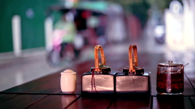 Table sauces and rainy street view from outdoor restaurant, Phnom Penh, Cambodia video