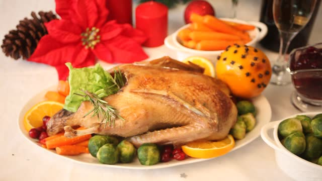 Table served for thanksgiving or Christmas dinner. Woman hand decorating stuffed roasted turkey. Traditional celebrating holiday