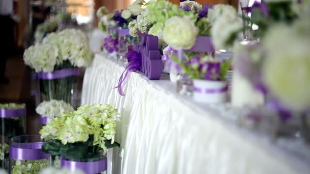 vidéos et rushes de réglage de la table lors d'une réception de mariage de luxe. décor avec fleur sur le repas de noces - ambiance événement