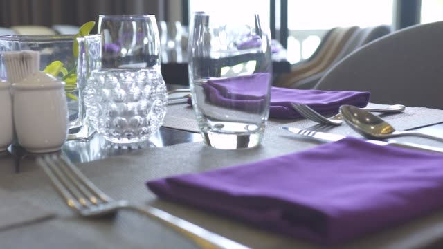 table setting restaurant concept. close up cotton cloth napkin, glasses, spoons, forks and knives on dining table luxury restaurant - łyżka sztućce filmów i materiałów b-roll