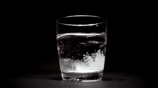 Tablet falls to the bottom of the glass with water a black background slow motion video