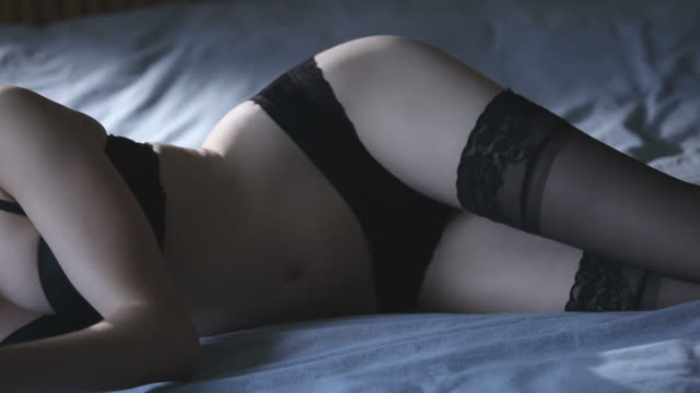 Tablet lingerie        LI CM INF Tracking shot of a beautiful young woman lying on a bed in underwear using a tablet PC (ipad), strongly backlit. seductive women stock videos & royalty-free footage