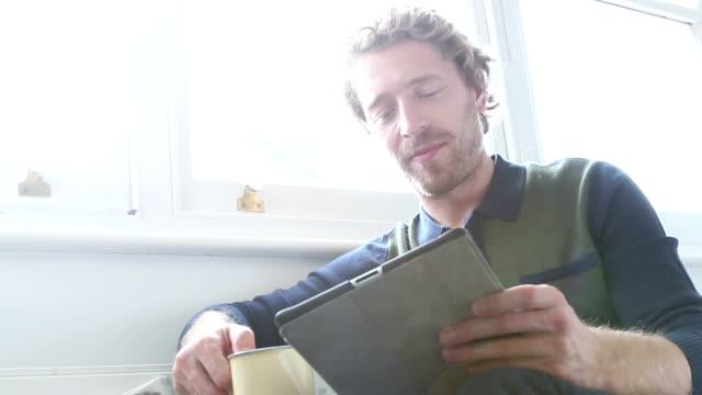 Tablet man, relaxing. Window. video