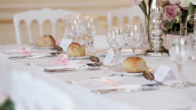 Tableware decor arrangement of festive table close up changing rack focus details. Wedding reception table with guest place cards set with glasses cutlery flowers and bread buns on dish plates ready video
