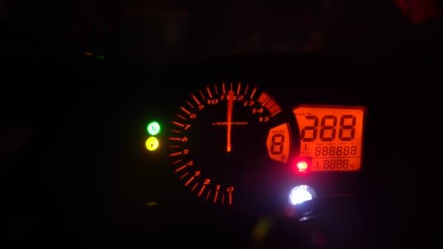 vidéos et rushes de tachymètre en lumière rouge montrant la vitesse rapide - moto sport