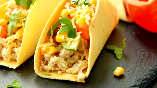 Tacos with lime, corn, chicken, pepper, tomato, avocado, cheese and parsley video