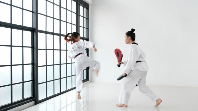 Taekwondo coach use kickpad or tools for training to her trainee in the gym with glass windows. The text show on belt and back of trainee mean taekwondo.