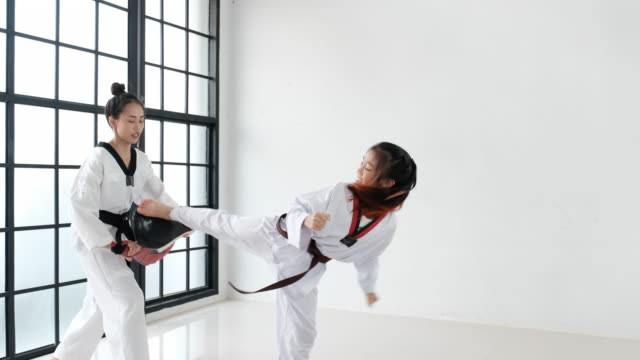 Taekwondo girl coach teach technique by using some tools to her student for front kick in gym.