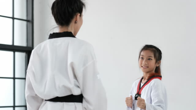 Taekwondo girl coach teach technique to her student for front kick in gym.