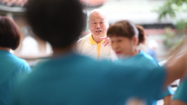 Tai Chi master instructing senior students with horsetail stick
