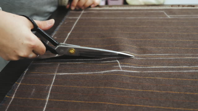 tailor at work. cutting costume fabric with scissors - tailor working video stock e b–roll