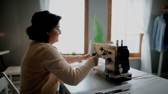 tailor at work on sewing machine in her tailor studio - cucire video stock e b–roll