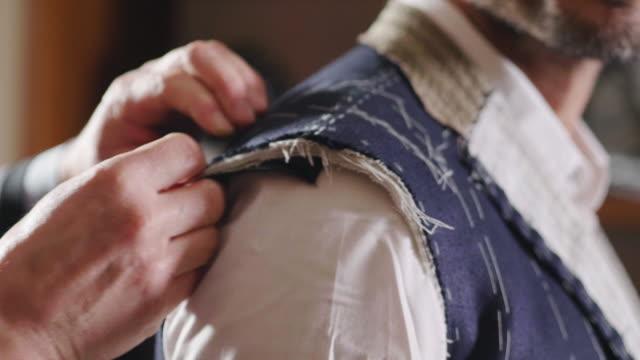 en skräddare skära en trasa enligt traditionen av skräddare. sömnads tillverkaren använder perfekt nål och tråd för att sy traditionella koncept, sy - skräddare bildbanksvideor och videomaterial från bakom kulisserna