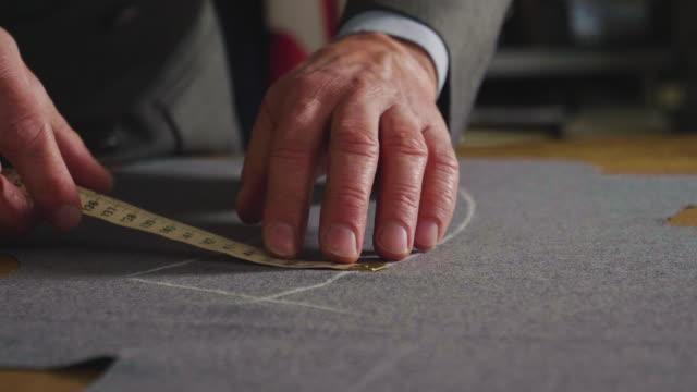 en skräddare ritning och skära en trasa enligt traditionen av skräddare. sömnads tillverkaren använder perfekt nål och tråd för att sy traditionella koncept, sy - skräddare bildbanksvideor och videomaterial från bakom kulisserna