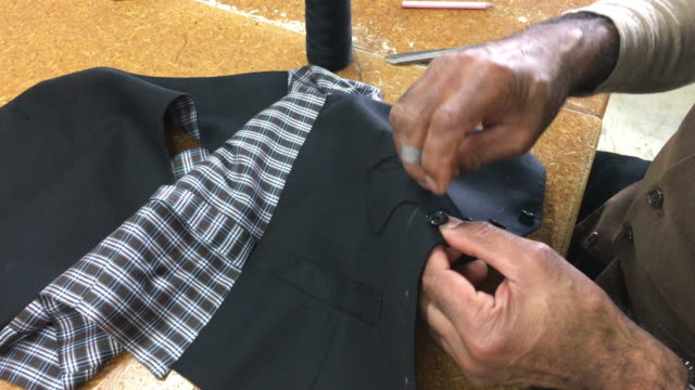 Tailor sewing a button video