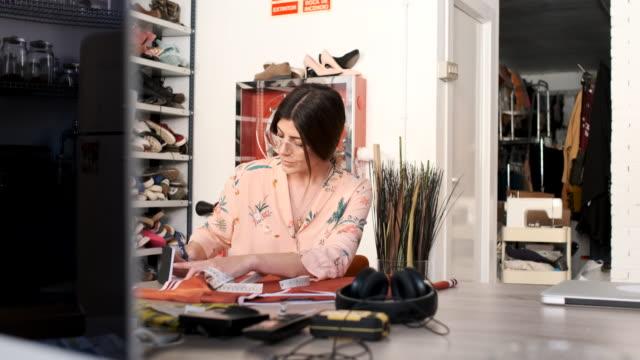 donna sartoriale che lavora in un ufficio per piccole imprese, nel design e nell'industria della moda. - sarta video stock e b–roll
