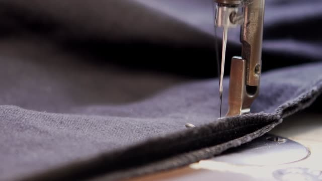 slow-mo: tailor working with sewing machine - cucire video stock e b–roll