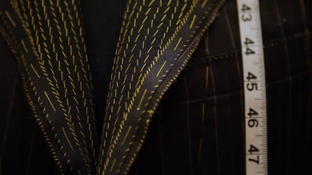 abiti da uomo su misura su un rack - manica video stock e b–roll