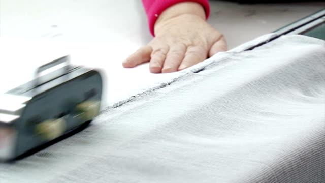 Bидео tailors cut gauze to produce face masks