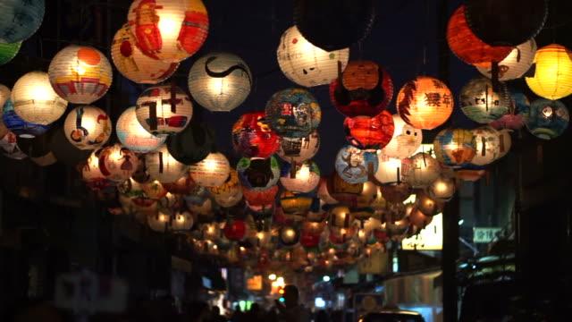 vidéos et rushes de festival des lanternes taïwanaises. enfants à main peints lanternes suspendus pendant la nuit, rue piétonne - nouvel an chinois