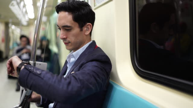 Taiwanese man sitting in subway train and reading newspaper Handsome Taiwanese man in suit sitting in subway train and reading newspaper, checking the time on wristwatch checking the time stock videos & royalty-free footage