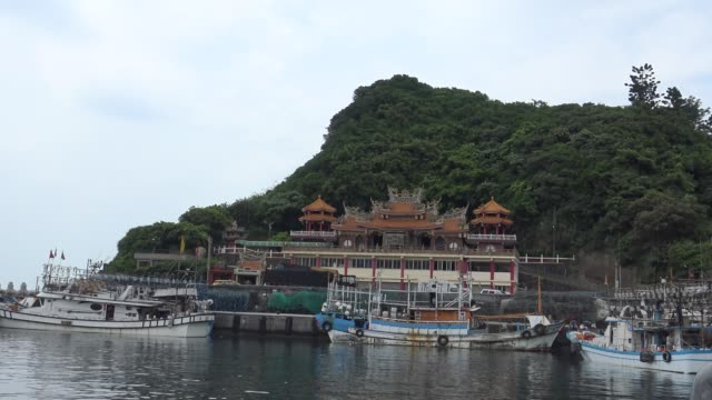 4K Taiwanese Temple of Matzu, in green mountain with fishing boats in port