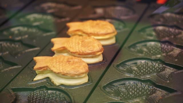 鯛焼き、日本の伝統的なデザート。小豆や他のものと鯛魚図形の塗りつぶしでパンケーキします。 ビデオ