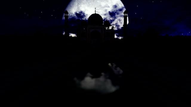 Taj Mahal at night against full moon, timelapse clouds video
