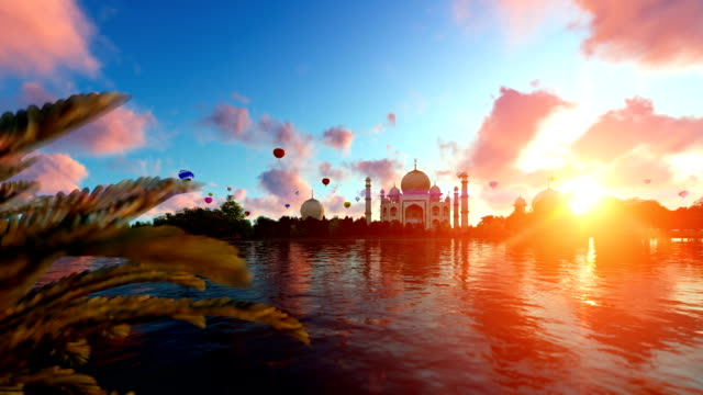 Taj Mahal, view from Yamuna River, hot air balloons flying against beautiful sunrise, tilt video