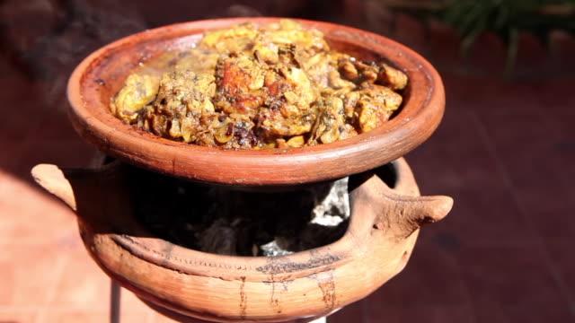 vídeos y material grabado en eventos de stock de tajine de pollo humeante cocinado en catarro de barro y con carbón - tiesto