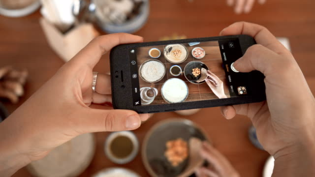 vídeos de stock, filmes e b-roll de tirar uma fotografia de comida em um restaurante com a câmera do telefone móvel para a rede social - blogar