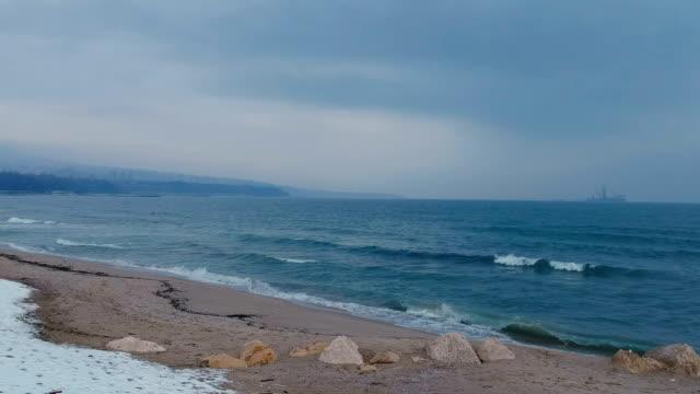 vídeos de stock e filmes b-roll de take off a drone view of black sea, sand, snow and a ship in winter - stock video - linha do horizonte sobre água