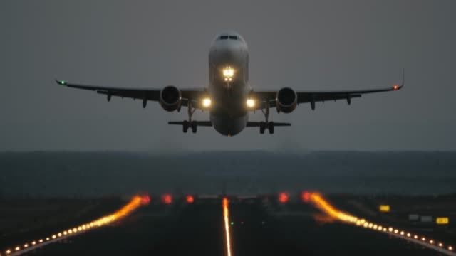 Take off at dawn A frontal shot of a lighted runway and an airplane, that is riding to the camera and then takes off airport runway stock videos & royalty-free footage