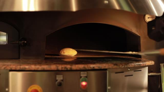 take one ready pita bread from hot oven - chleb pita filmów i materiałów b-roll