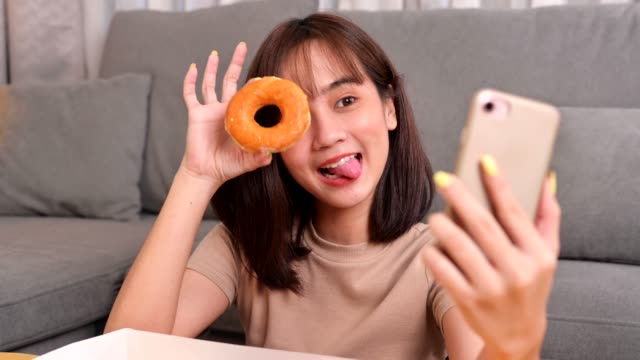 take photo of donut for social online site. fast food delivery and takeaway back home. eating donut when takeout and delivery. asian woman lifestyle in living room. - food delivery стоковые видео и кадры b-roll
