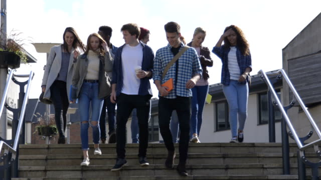 Take the Steps Group of Students walking down steps in a city. They are wearing casual clothing and smiling. students stock videos & royalty-free footage