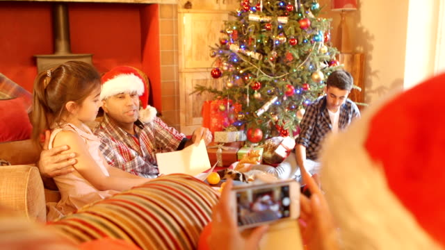 vídeos de stock e filmes b-roll de taking a picture of family opening presents and cards at christmas - man admires forest