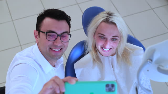 Taking A Selfie Dentist and patient taking a selfie with mobile phone. russian ethnicity stock videos & royalty-free footage