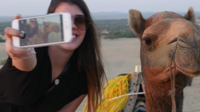 vidéos et rushes de prenant un selfie avec chameau dans le désert - photophone