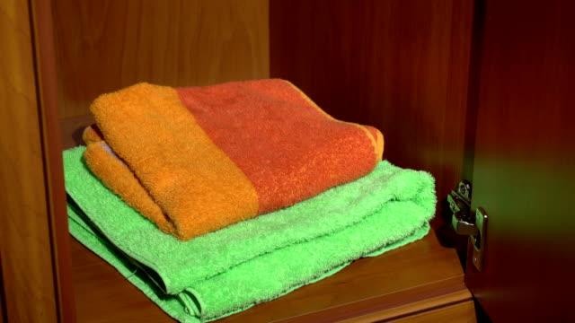 med en uppsättning handdukar från en garderob - looking inside inside cabinet bildbanksvideor och videomaterial från bakom kulisserna