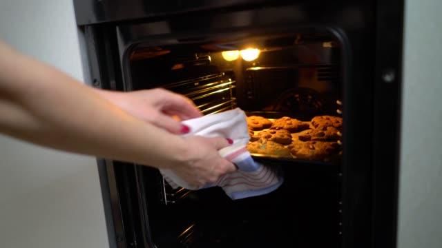 vídeos de stock e filmes b-roll de taking baking tray with baked cookies out of electric oven - christmas cooking