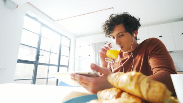 frühstück während der verwendung einer digitalen-tablets nehmen. - orangensaft stock-videos und b-roll-filmmaterial