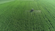istock Taking care of the Crop. Aerial view of a Tractor fertilizing a cultivated agricultural field. 1201456831