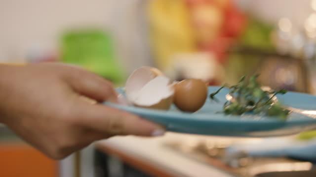 vídeos de stock e filmes b-roll de taking egg shales and tomato stem and throwing them away - economia circular
