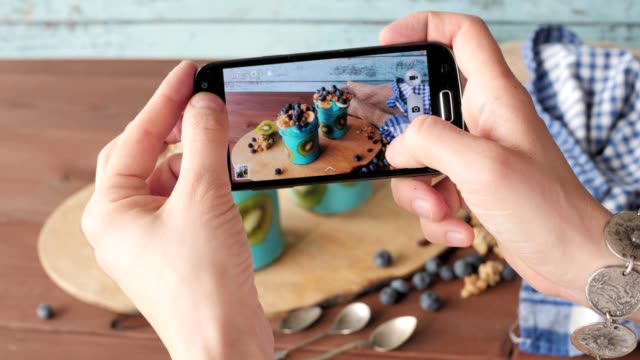taking food photo with cellphone, blue majik smoothie, superfood - adulazione video stock e b–roll