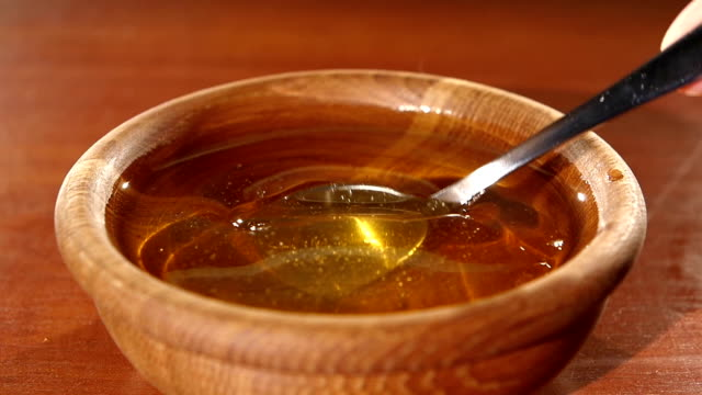 Taking honey by metal spoon in wooden bowl, slow motion video