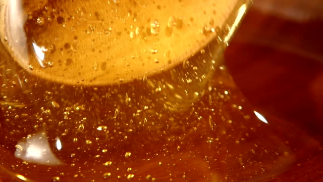 Taking honey by using spoon in wooden bowl, slow motion, close up video