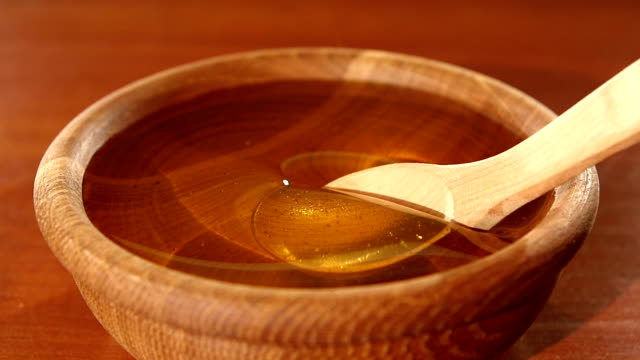 Taking honey by using spoon in wooden bowl, slow motion video